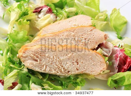 Three slices of baked chicken meat on fresh lettuce leaves