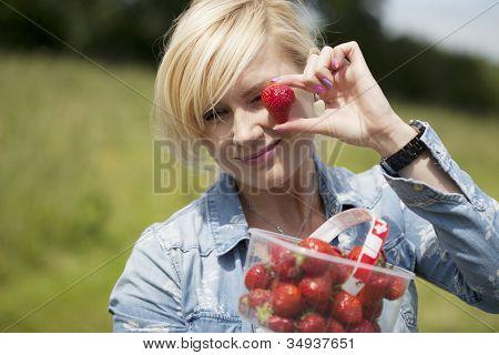 Attraktive blonde Frau hält große eine Reife rote Erdbeere in den Fingern aus einer vollen Schale-tha