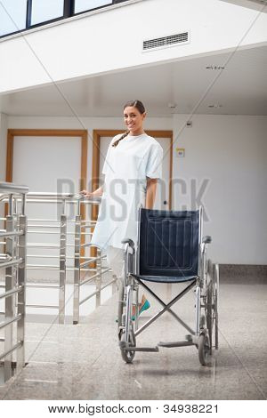 Smiling patient standing next to a wheelchair in hospital hallway