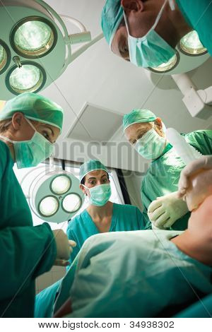 Medical team working on a bleeding patient in a surgical room