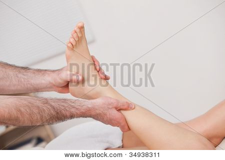 Podiatrist manipulating the ankle of his patient while holding it indoors