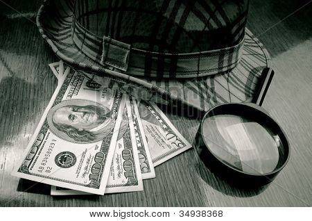 American Dollar-bills, loupe and hat on the wooden table