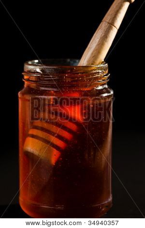 Honey dipper in a honey jar against a black background