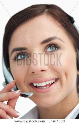 Blue eyed businesswoman with headset looking up against white background