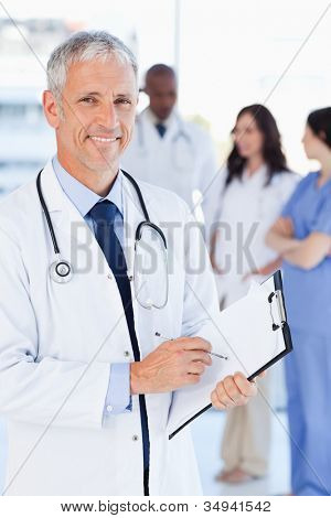 Mature doctor showing a great smile while pointing to a word on his clipboard