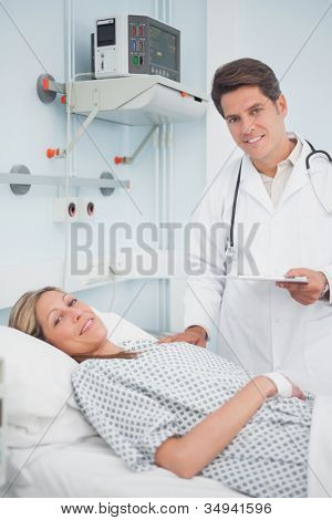 Doctor and patient smiling in hospital ward