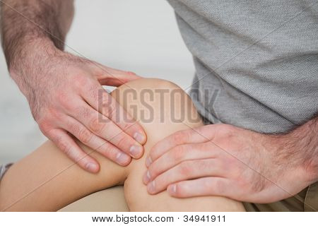 Physiotherapist massaging a painful knee in a room