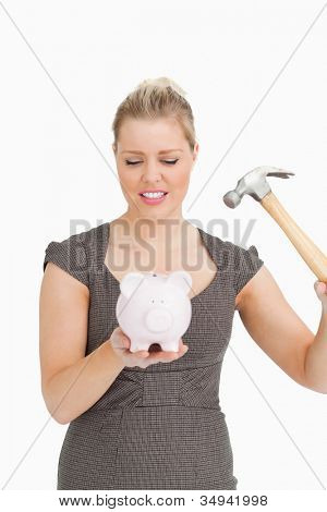 Serious woman with a piggy bank and a hammer against white background