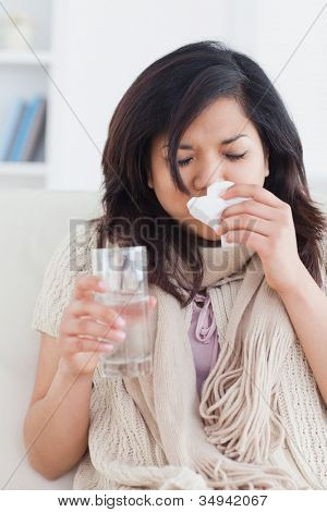 Sick woman blowing her nose in a living room
