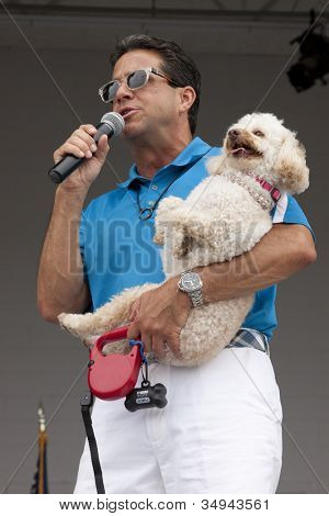 RIDGEFIELD PK, NJ-JULY 14: ABC Channel 7 meteorologist and dog lover, Bill Evans, holding his own dog, speaks to an audience at the 2nd Annual Bark In The Park on July 14, 2012 in Ridgefield Park, NJ.