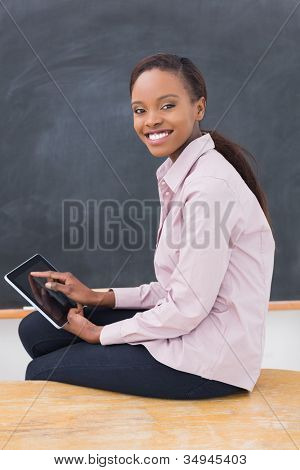 Teacher sitting on desk while holding a tablet computer in a classroom
