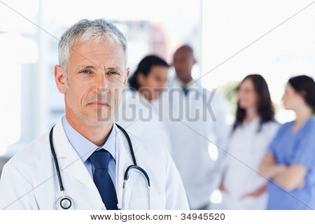 Mature doctor looking straight ahead with a serious look on his face while his team is behind him