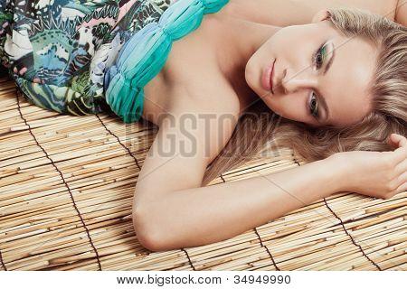 woman laying on bamboo mat
