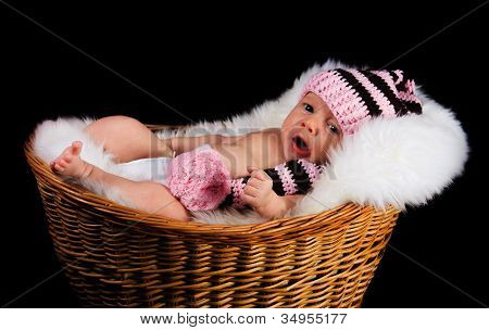 Newborn Child in a wicker basket on a black background.