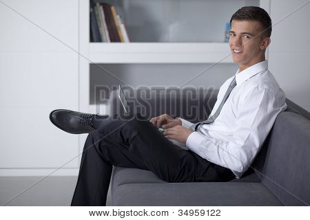 Smiling Businessman Working With A Notebook And Sitting On Couch In Office
