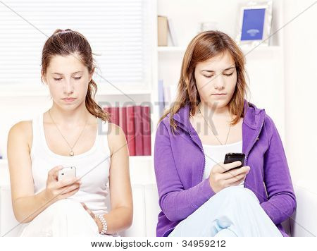 Two Teenage Girs With Mobile Phones