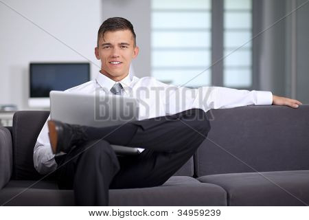 Successfull Businessman Working With A Notebook And Sitting On Couch In Office
