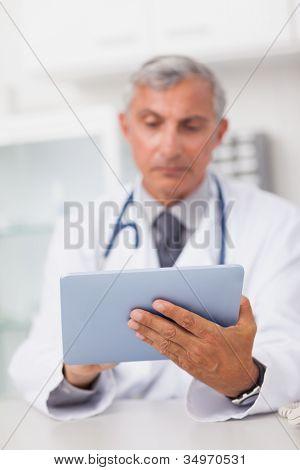 Médico, segurando um computador tablet ao usá-lo em um consultório médico