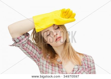 Woman wearing cleaning gloves while wiping her brow against white background