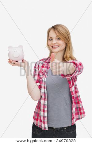 Woman smiling while holding a piggy bank against a white background