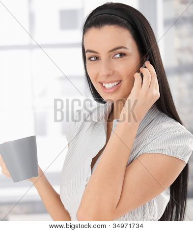 Happy woman laughing making mobile phone call holding coffee mug.