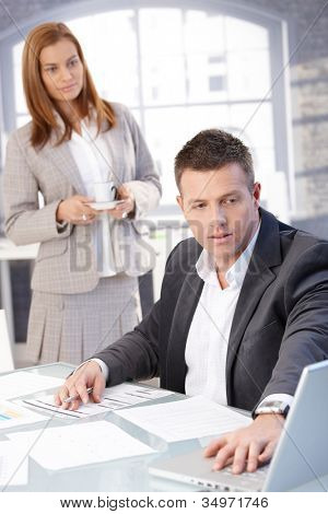 Handsome businessman working at desk, using laptop, assistant bringing coffee.