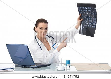 Doctor pointing at x-ray image, explaining scan, sitting in office, smiling.