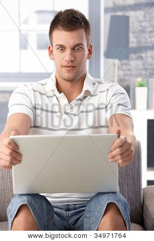 Young man sitting at home using laptop, staring at screen shocked.