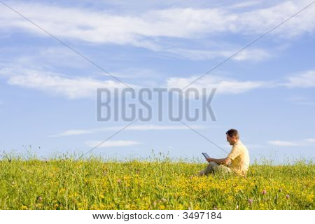 Man With Laptop On Meadow