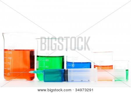 Five beakers behind a syringe against a white background