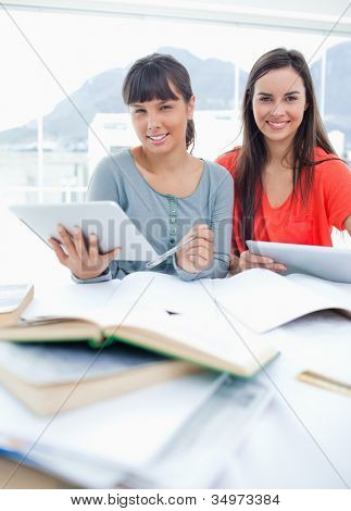 Two smiling students sit together at the table with tablets in their hands as they do homework
