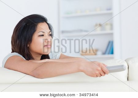 Woman pressing on a television remote while sitting on a white couch in a living room