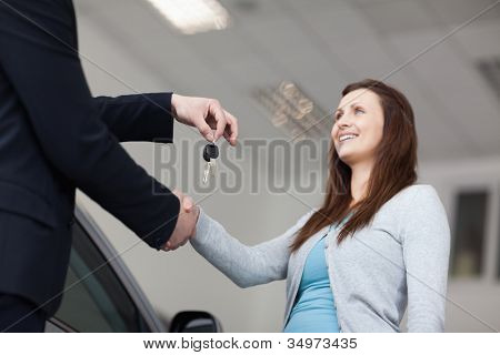 Client receiving keys car while shaking hand  in a garage