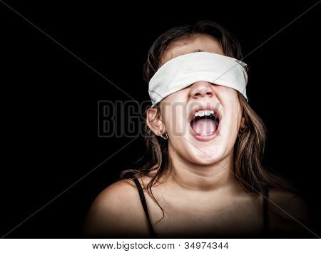 Small girl screaming with her eyes blindfolded with a handkerchief isolated on black with space for text