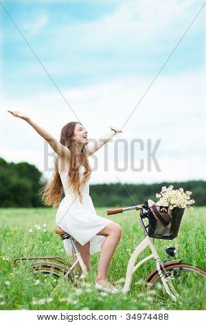 Bicicleta de mujer a caballo en el campo de flores silvestres