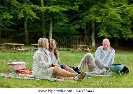 Caucasian friends relaxing at an outdoor picnic in forest park