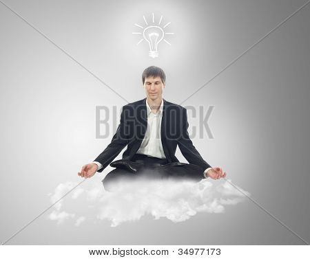 Businessman In Lotus Position On A Cloud With A Light Bulb Over Your Head