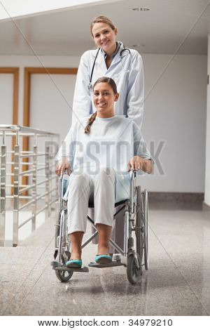 Doctor and patient looking at camera in hospital hallway