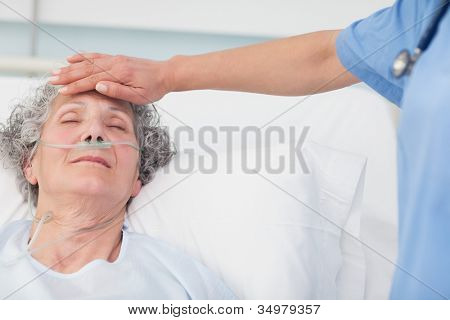 Nurse putting her hand on the forehead of a patient in hospital ward