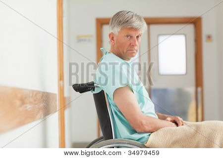 Man sitting in a wheelchair while looking at camera in hospital ward