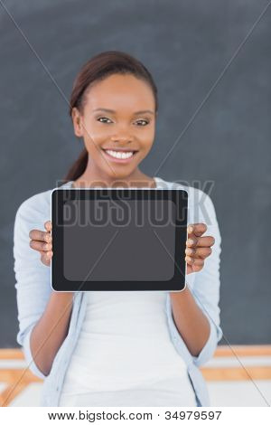 Smiling black woman holding a tablet computer in a classroom