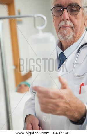 Doctor checking an intravenous drip in hospital ward