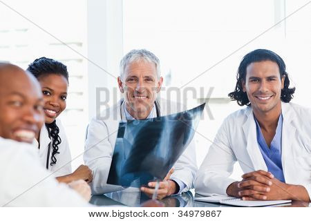 Smiling doctor surrounded by three younger colleagues holding an x-ray of lungs