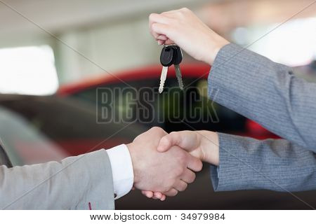 Close up of a woman shaking hand to a man in a dealership