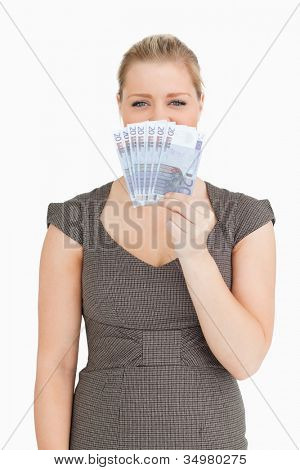 Pretty woman hiding her mouse with euro banknotes against white background