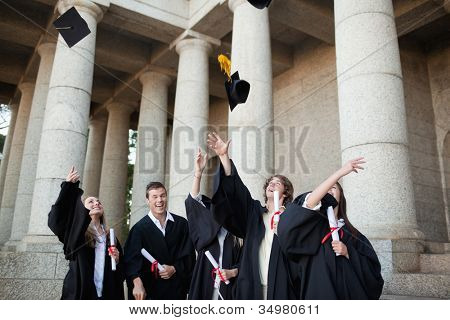 Graduates throwing their hats in the sky in front of their university