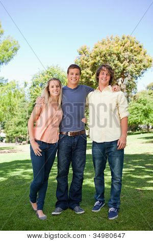 Three smiling students standing in a park together