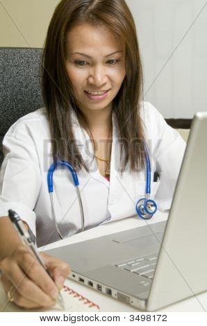 Doctor Writing At Her Desk