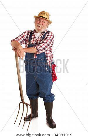 Cheerful Senior Farmer Leaning On Hay Fork