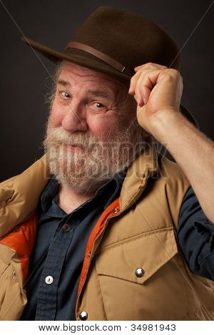 Friendly senior man tipping his hat in greeting